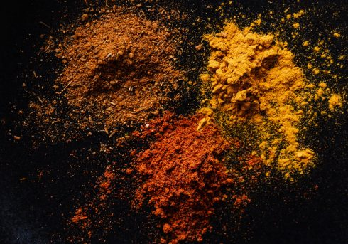 assorted colorful dry powdered spices on black background